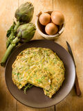 Omelette with artichokes. On wood background Royalty Free Stock Photography