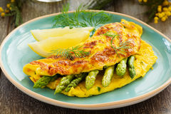 Omelette with asparagus. On a blue plate royalty free stock photos