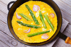 Omelette with Asparagus and Red Onion in Pan. View from above, top studio shot. Stock Images