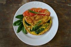 Omelette avec des oeufs, des pommes de terre et des épinards Images stock