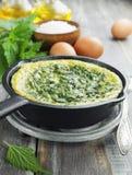 Omelette avec des orties dans la casserole Photographie stock libre de droits