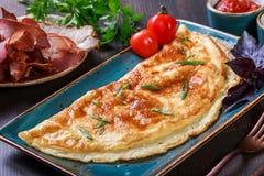 Omelette avec la sauce de prosciutto, de tranches jambon, de champignons, de verts, de fromage et tomate sur le fond en bois fonc images stock