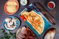 Omelette avec la sauce de prosciutto, de tranches jambon, de champignons, de verts, de fromage et tomate sur le fond en bois fonc image stock
