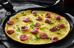 Omelette avec la saucisse dans une poêle sur la table en bois Image stock