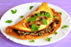 Omelette avec les champignons frits, le fromage et le persil frais Photographie stock