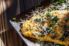 Omelette avec les herbes, le Basil et le parmesan et l'ail image stock