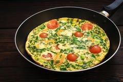 Omelette avec les tomates-cerises, le poivron doux et les herbes pour 2 personnes Photographie stock