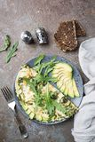Omelette with avocado and arugula. On gray ceramic plate on stone background, top view. Healthy breakfast stock photography