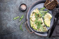 Omelette with avocado and arugula. On gray ceramic plate on stone background, top view. Healthy breakfast stock images