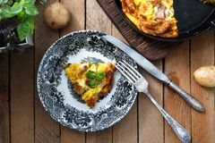 Omelette with bacon, potato, leeks and cheese on a plate, top view Stock Photography