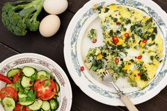 Omelette with broccoli, chili and greens served with tomato and Stock Images