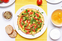 Omelette with broccoli, tomato and green herbs Royalty Free Stock Photography