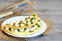 Omelette casalinga dell'uovo farcita con i cubi del tofu ed il prezzemolo fresco su un bordo di legno Forcella, coltello, tessuto Fotografia Stock