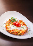 Omelette with cheese tomato ham and rucola. Omelette with cheese, cherry tomato, ham and rucola on plate on wooden table Stock Photo