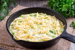 Omelette con la cipolla ed il formaggio in una padella fotografie stock