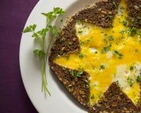Omelette con pane integrale e prezzemolo a forma di stella sulla tovaglia porpora Fotografia Stock