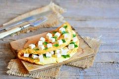 Omelette de tofu Omelette végétarienne bourrée des cubes en tofu et du persil frais sur un conseil en bois Couverts, textile de t Images stock