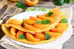 Omelette douce d'abricot Omelette bourrée avec les abricots frais d'un plat blanc et d'un vieux fond en bois Petit déjeuner facil Photographie stock libre de droits