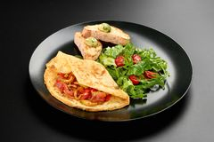Omelette eggs fryed tomatoes rucola bread in a plate on dark background with copy space menu breakfast food royalty free stock image