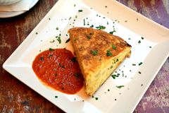 Omelette espagnole de déjeuner traditionnel avec de la sauce chaude d'un plat Photo stock