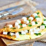 Omelette farcita casalinga Omelette fritta farcita con i cubi del tofu ed il prezzemolo fresco su un bordo di legno Coltelleria,  Fotografie Stock