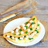 Omelette farcita sana Omelette fritta farcita con i cubi del tofu ed il prezzemolo fresco su un piatto e su una tavola di legno C Fotografie Stock