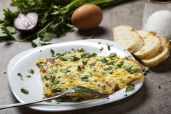 Omelette fatta dalle uova, dal bacon, dal formaggio e dalla cipolla Immagini Stock
