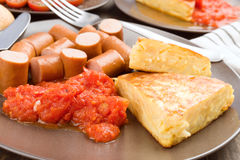 Omelette with frankfurter and tomato in clay dish. On wood Royalty Free Stock Photo