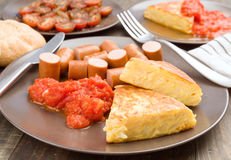Omelette with frankfurter and tomato in clay dish. On wood Stock Images