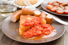 Omelette with frankfurter and tomato in clay dish. On wood Stock Image