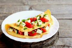 Omelette frite bourrée du fromage, des tomates et du persil Omelette bourrée d'un plat et sur le vieux fond en bois Omelette faci Photo stock