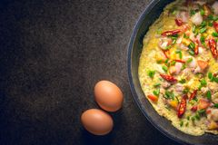 Omelette in frying pan on dark background, top view. garlic and Royalty Free Stock Photography