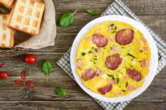 Omelette with ham, salami, cheese and greens on a plate on a wooden background. royalty free stock photos