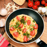 Omelette with ham, tomatoes and chees on the frying pan. Royalty Free Stock Photos
