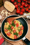 Omelette with ham, tomatoes and chees on the frying pan. Royalty Free Stock Images