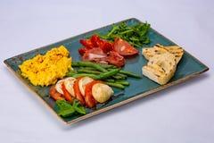 Omelette italiana dello spuntino con il aspagagus, il pomodoro, la rucola, il salame, il prosciutto di Parma ed il pane tostato fotografia stock libera da diritti