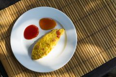 Omelette and ketchup decorated as funny face on white plate. Funny breakfast. stock photography