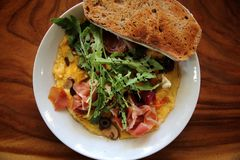 Omelette with parma ham and salad. On a plate royalty free stock photo