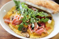 Omelette with parma ham and salad. On a plate royalty free stock images
