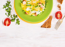 Omelette  with  peas, potatoes and sausages in green plate Royalty Free Stock Images