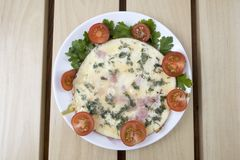 Omelette on a plate. Cooked omelette with ham tomatoes and greens on a plate stock photo