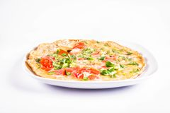 Omelette on a plate. Omelette with tomatoes and fresh corn salad on a white background royalty free stock photo