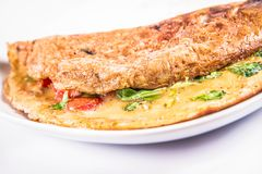 Omelette on a plate. Omelette with tomatoes and fresh corn salad on a white background royalty free stock photography