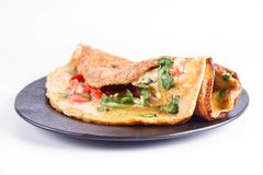 Omelette on a plate. Omelette with tomatoes and fresh corn salad on a white background stock photography