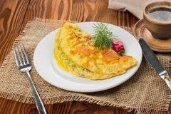 Omelette on a plate, wooden table. Stock Images