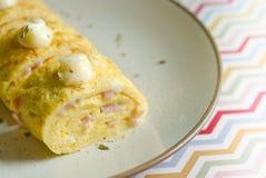 Omelette rolka na beżu talerzu nad kolorowym papierem Obrazy Stock