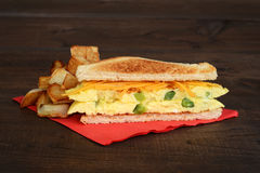 Omelette sandwich with fries on red napkin Royalty Free Stock Images