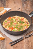 Omelette with sausage, onion, herbs and tomatoes Royalty Free Stock Photos