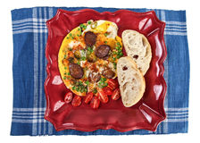 Omelette with sausage on plate and blue table mat Stock Photography