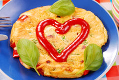 Omelette with sausage and red paprika. Omelette with frankfurter sausage and red paprika decorated ketchup heart stock image